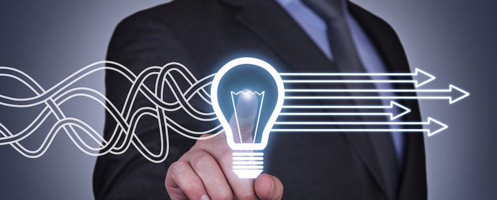 Man with finger on lightbulb that organizes wavy lines into straight arrows
